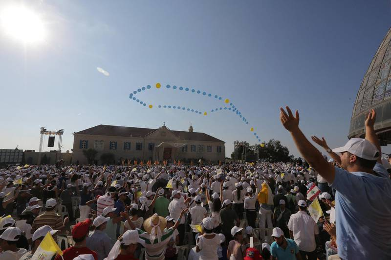 Lebanese Catholic youths cheer Pope Benedict XVI upon his arrival to the Maronite patriarchat in Bkerke on September 15, 2012. Pope Benedict XVI urged Middle Eastern Christians and Muslims to forge a harmonious, pluralistic society in which the dignity of each person is respected and the right to worship in peace is guaranteed. AFP PHOTO / JOSEPH EID (Photo by JOSEPH EID / AFP)