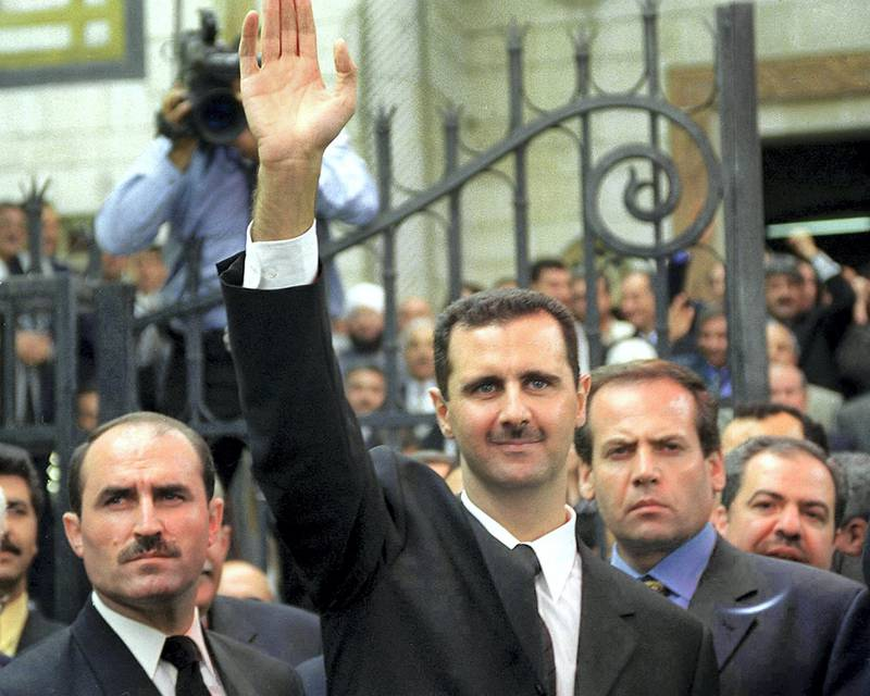(FILES) In this file photo taken on July 17, 2000, Syria's new President Bashar al-Assad (C) waves to supporters outside the parliament in the capital Damascus. - President Bashar al-Assad, whose family has ruled Syria for over half a century, faces an election this week meant to cement his image as the only hope for recovery in the war-battered country, analysts say. (Photo by Louai Beshara / AFP)