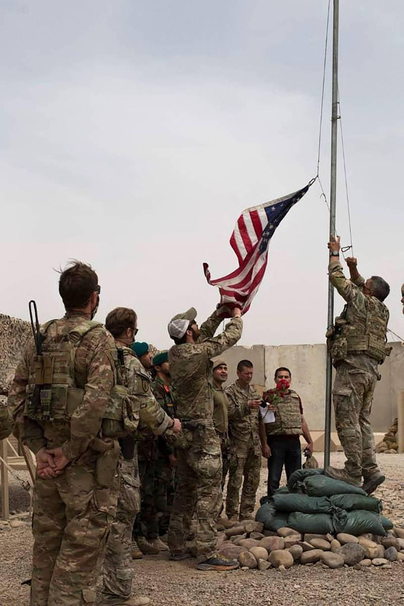 """This handout photograph taken on May 2, 2021 and released by Afghanistan's Ministry of Defense shows US soldiers lowering the US national flag during a handover ceremony to the Afghan National Army (ANA) army 215 Maiwand corps at Antonik camp in Helmand province. RESTRICTED TO EDITORIAL USE - MANDATORY CREDIT """"AFP PHOTO /Afghanistan's Ministry of Defense"""" - NO MARKETING - NO ADVERTISING CAMPAIGNS - DISTRIBUTED AS A SERVICE TO CLIENTS  / AFP / Afghanistan's Ministry of Defence office / - / RESTRICTED TO EDITORIAL USE - MANDATORY CREDIT """"AFP PHOTO /Afghanistan's Ministry of Defense"""" - NO MARKETING - NO ADVERTISING CAMPAIGNS - DISTRIBUTED AS A SERVICE TO CLIENTS"""