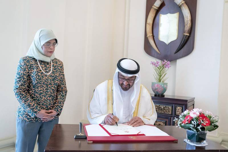 SINGAPORE, SINGAPORE - February 28, 2019: HH Sheikh Mohamed bin Zayed Al Nahyan, Crown Prince of Abu Dhabi and Deputy Supreme Commander of the UAE Armed Forces (R) sings a visitors book, prior to a meeting at, at the Istana presidential palace. Seen with HE Halimah Yacob, President of Singapore (L). ( Mohamed Al Hammadi / Ministry of Presidential Affairs ) ---