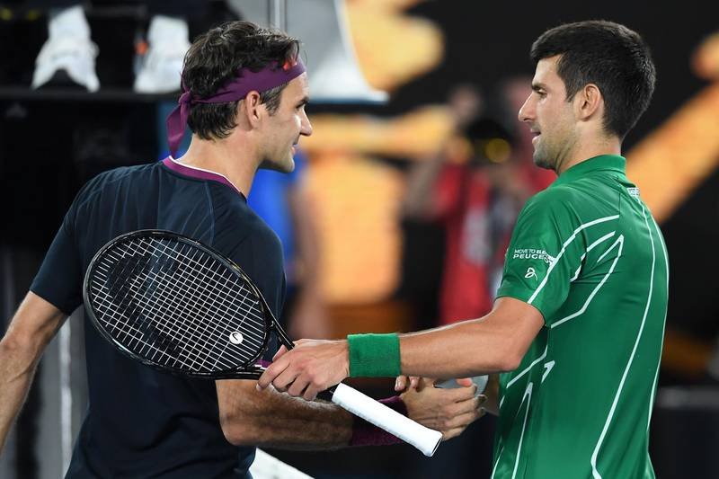 Serbia's Novak Djokovic (R) shakes hands with Switzerland's Roger Federer at the end of their men's singles semi-final match on day eleven of the Australian Open tennis tournament in Melbourne on January 30, 2020. IMAGE RESTRICTED TO EDITORIAL USE - STRICTLY NO COMMERCIAL USE  / AFP / Greg Wood / IMAGE RESTRICTED TO EDITORIAL USE - STRICTLY NO COMMERCIAL USE