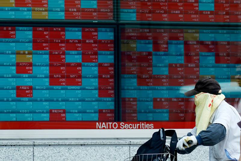 A man riding a bicycle looks at an electronic stock board showing Japan's Nikkei 225 index at a securities firm in Tokyo Thursday, Aug. 29, 2019. Asian stocks declined Thursday following Wall Street's rebound amid uncertainty about U.S.-Chinese trade tension. (AP Photo/Eugene Hoshiko)