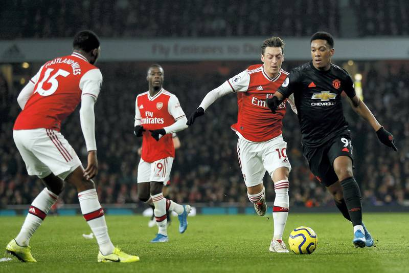 Manchester United's French striker Anthony Martial (R) vies with Arsenal's German midfielder Mesut Ozil (2nd R) ans Arsenal's English midfielder Ainsley Maitland-Niles (L) during the English Premier League football match between Arsenal and Manchester United at the Emirates Stadium in London on January 1, 2020. - Arsenal won the game 2-0. (Photo by Ian KINGTON / IKIMAGES / AFP) / RESTRICTED TO EDITORIAL USE. No use with unauthorized audio, video, data, fixture lists, club/league logos or 'live' services. Online in-match use limited to 45 images, no video emulation. No use in betting, games or single club/league/player publications.