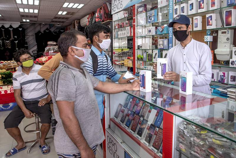 Abu Dhabi, United Arab Emirates, April 23, 2020.  Customers at a mobile phone shop at the Mussafah 32 area during the Coronavirus pandemic.Victor Besa / The NationalSection:  NAFor: stock images and standalone