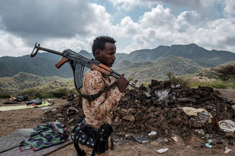 (FILES) In this file photo taken on December 09, 2020 A member of the Afar Special Forces stands in front of the debris of a house in the outskirts of the village of Bisober, Tigray Region, Ethiopia. Several houses in the village were damaged during the confrontations between the Tigray Forces and the Ethiopian Defense Forces. It has been six months since Ethiopian Prime Minister Abiy Ahmed sent troops into the country's northernmost Tigray region for a military campaign he vowed would be swift and targeted.  However the violence rumbles on and reports continue to emerge of massacres, rape and widespread hunger. / AFP / EDUARDO SOTERAS