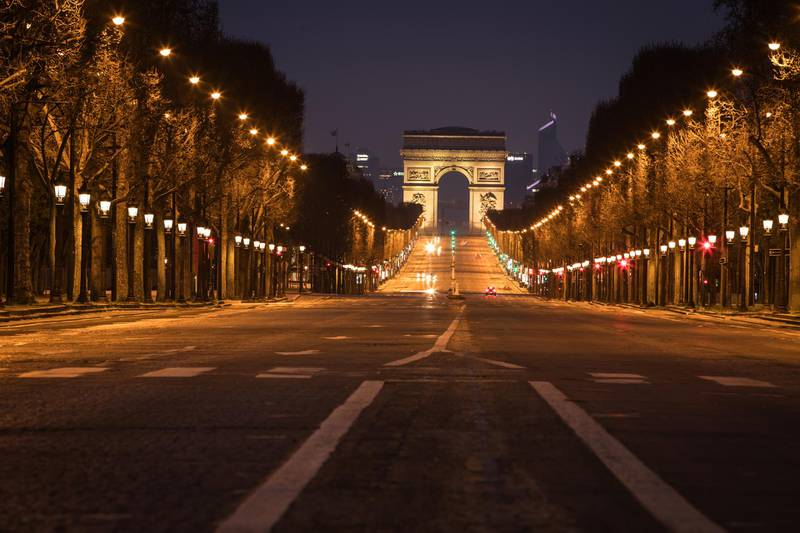 Street lights illuminate a deserted Champs Elysees leading to the Arc de Triumph monument  in central Paris on March 21, 2020, as a strict lockdown is in effect across France to stop the spread of COVID-19, caused by the novel coronavirus. - A strict lockdown requiring most people in France to remain at home came into effect at midday on March 17, 2020, prohibiting all but essential outings in a bid to curb the coronavirus spread. The government has said tens of thousands of police will be patrolling streets and issuing fines of 135 euros ($150) for people without a written declaration justifying their reasons for being out. (Photo by JOEL SAGET / AFP)