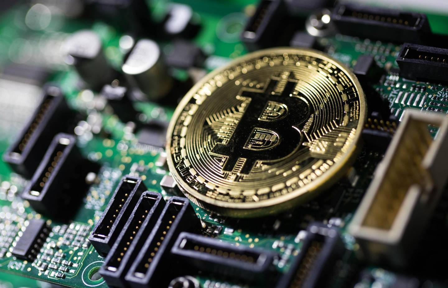 FILE: A coin representing Bitcoin cryptocurrency sits on a computer circuit board in this arranged photograph in London, U.K., on Tuesday, Feb. 6, 2018. The great cryptocurrency crash of 2018 is heading for its worst week yet. Bitcoin sank toward $4,000 and most of its peers tumbled on Friday, extending the Bloomberg Galaxy Crypto Index's weekly decline to 25 percent. That's the worst five-day stretch since crypto-mania peaked in early January. Photographer: Chris Ratcliffe/Bloomberg