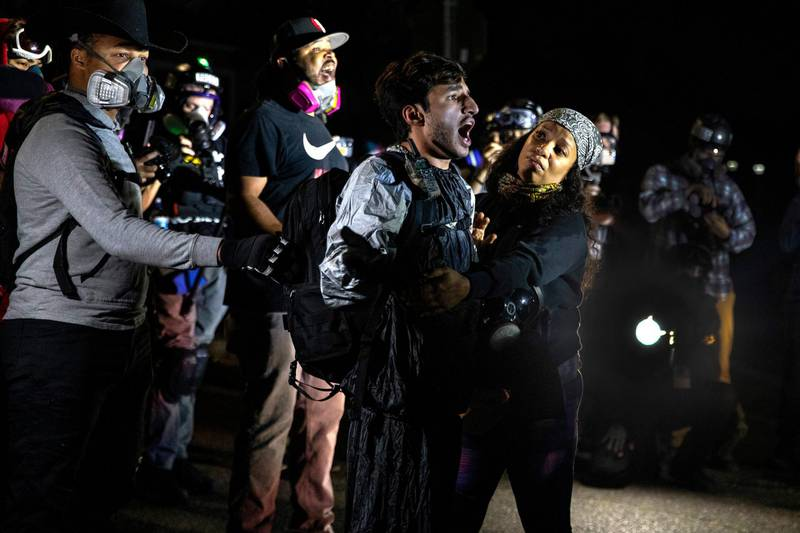 A protester screams at police as they attempt to take control of the streets with Portland protests reaching 100 consecutive nights on Saturday, Sept. 5, 2020, in Portland, Ore. Hundreds of people gathered for rallies and marches against police violence and racial injustice Saturday night in Portland, Oregon, as often violent nightly demonstrations that have happened for 100 days since George Floyd was killed showed no signs of ceasing.(AP Photo/Paula Bronstein)
