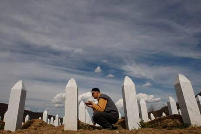 Bosnian Muslim man says a prayer in front of the grave stone of his relative at Memorial Center of Potocari, near Srebrenica, 70 kms norteast of Bosnian capital of Sarajevo, on Thursday April 1, 2010.  Serbia's parliament has apologized to the Bosnian Muslim victims of the 1995 Srebrenica massacre Wednesday, ending years of denial, a move which is being seen as a crucial part for reconciliation in the war-scarred Balkans. (AP Photo/Amel Emric) *** Local Caption ***  XAE107_BOSNIA_SREBRENICA_SRBIJA_APOLOGIZE.jpg