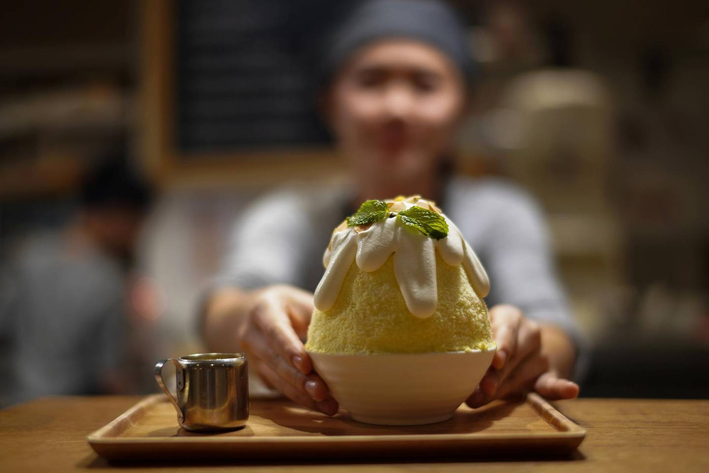 """A waitress serves a """"Durian Sticky rice kakigori"""" at an After You dessert cafe at a department store in Bangkok, Thailand, May 3, 2018. Picture taken May 3, 2018. REUTERS/Athit Perawongmetha"""