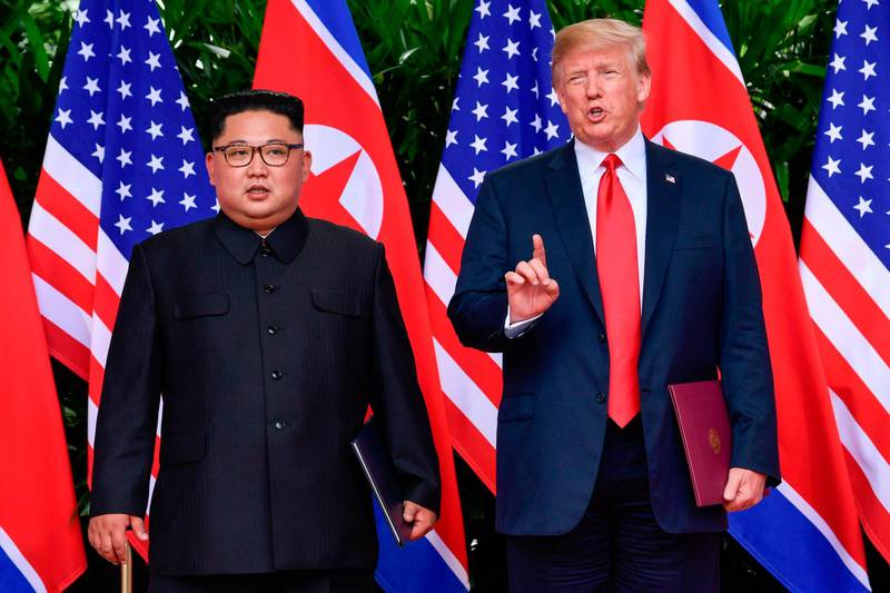 TOPSHOT - US President Donald Trump makes a statement before saying goodbye to North Korea leader Kim Jong Un (L) after their meetings at the Capella resort on Sentosa Island in Singapore on June 12, 2018.  Donald Trump and Kim Jong Un became on June 12, the first sitting US and North Korean leaders to meet, shake hands and negotiate to end a decades-old nuclear stand-off. / AFP / POOL / Susan Walsh