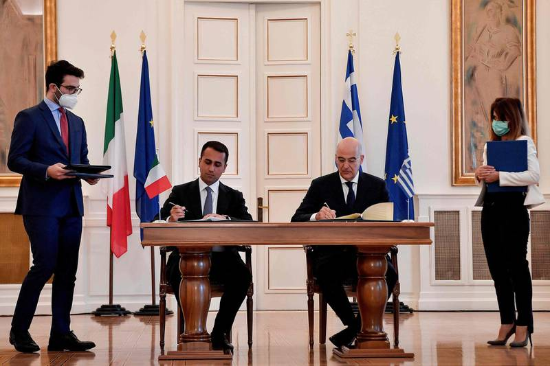 Greek Foreign Minister Nikos Dendias (R) and his Italian counterpart Luigi Di Maio sign a maritime zone agreement at the Foreign Ministry in Athens on June 9, 2020.  / AFP / Louisa GOULIAMAKI