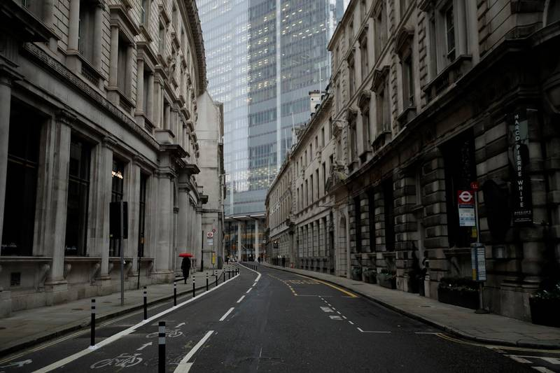 FILE - In this London, Jan. 5, 2021 file photo a person walks with an umbrella in light rain in the City of London financial district on the first morning of England entering a third national lockdown since the coronavirus outbreak began. British Prime Minister Boris Johnson on Monday night announced a tough new stay-at-home order, as authorities struggle to stem a surge in COVID-19 infections that threatens to overwhelm hospitals around the U.K. (AP Photo/Matt Dunham, File)