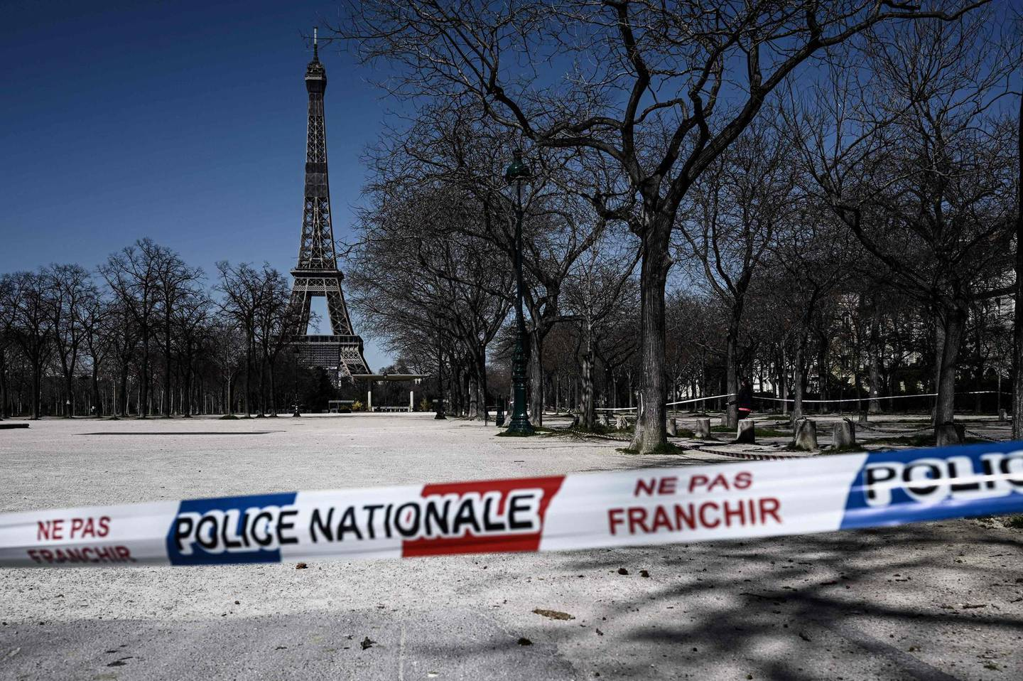 TOPSHOT - A limit set up by the national police is seen at the entrance of a closed park in front of the Eiffel tower in Paris  on March 23, 2020, as the country is under lockdown to stop the spread of Covid-19 disease caused by the novel coronavirus.  / AFP / PHILIPPE LOPEZ
