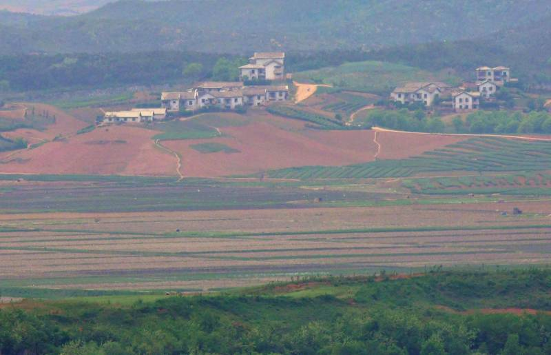 """North Korea's border county of Kaepoong is seen from a South Korean observation post in Paju near the Demilitarized Zone (DMZ) dividing the two Koreas on May 17, 2019. North Korea is experiencing its worst drought in over a century, official media reported on May 17, days after the World Food Programme expressed """"serious concerns"""" about the situation in the country.   / AFP / Jung Yeon-je"""