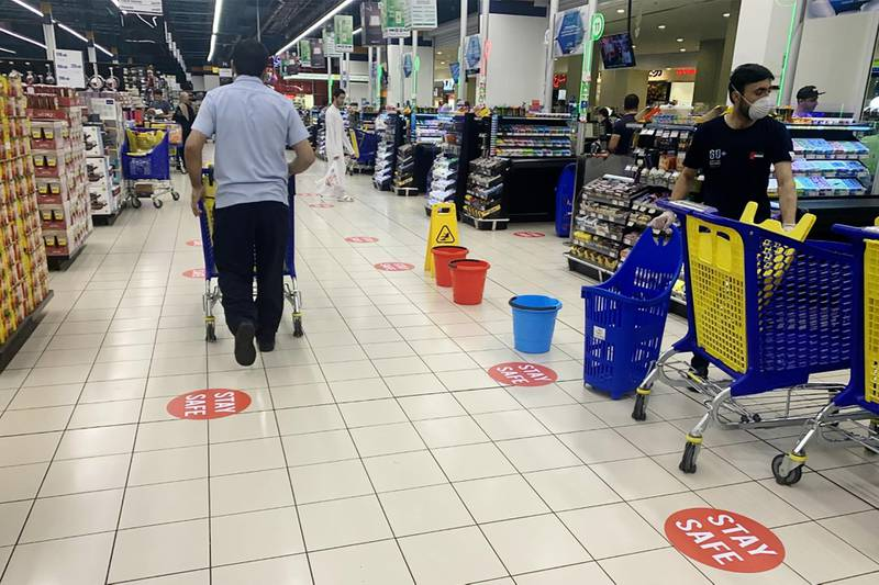 """This picture taken on March 22, 2020 in Dubai shows a view of distance stickers reading """"stay safe"""" placed along aisles at a supermarket, marking safe distances for shoppers to facilitate """"social distancing"""" methods as part of safety measures during the COVID-19 coronavirus pandemic.  / AFP / KARIM SAHIB"""
