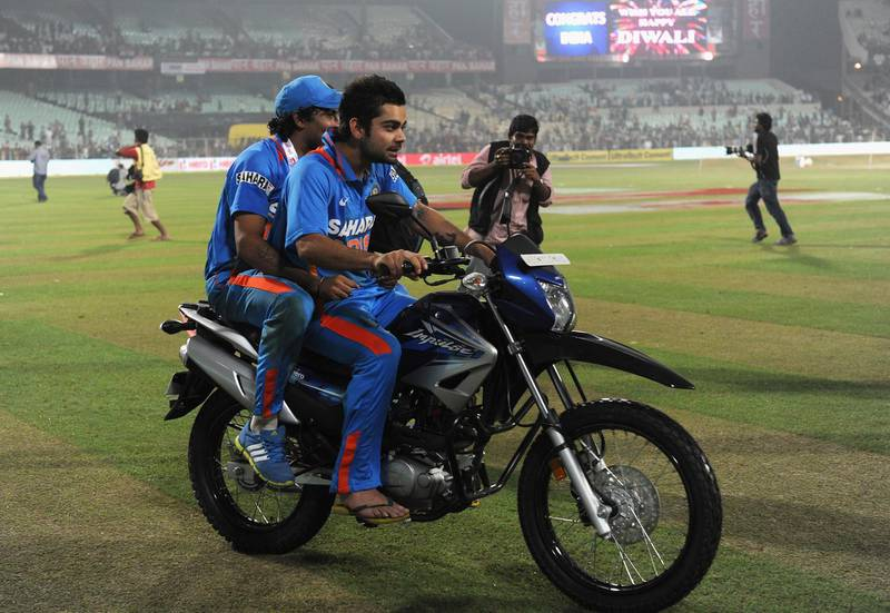 KOLKATA, INDIA - OCTOBER 25: Virat Kohli and Ravindra Jadeja of India celebrates by doing a lap of honour on the man of the match's motorbike after the 5th One Day International between India and England, at Eden Gardens on October 25, 2011 in Kolkata, India.  (Photo by Gareth Copley/Getty Images)
