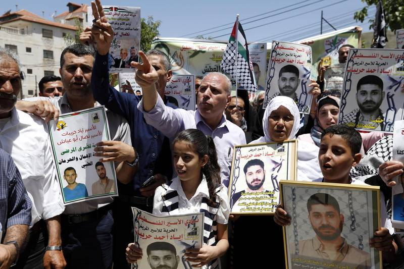 epa06827376 Palestinians hold posters in solidarity with detained Palestinians in Israel, during a protest demanding the release of Palestinian prisoners from Israeli jails, outside the Red Cross building in the West Bank city of Hebron, 21 June 2018.  EPA/ABED AL HASHLAMOUN