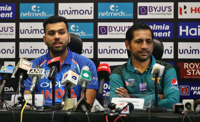 Captains of India Rohit Sharma, left, and Pakistan Sarfraz Ahmed listen to a question from a journalist during a press conference ahead of Asia Cup cricket at Dubai International Cricket Stadium in Dubai, United Arab Emirates, Friday, Sept. 14, 2018. (AP Photo/Aijaz Rahi)