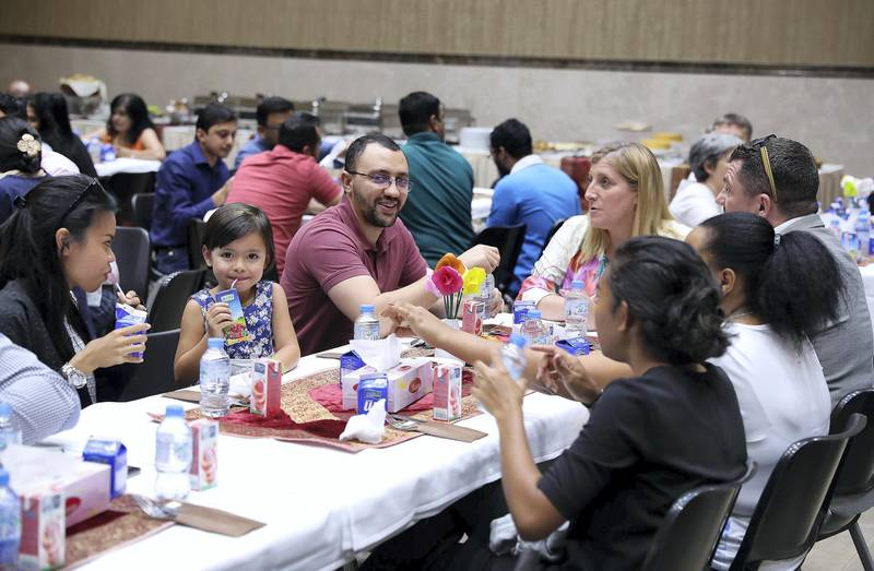 ABU DHABI , UNITED ARAB EMIRATES , JUNE 06 – 2018 :- People having their food during the iftar held at St Andrew's Church in Abu Dhabi.  ( Pawan Singh / The National )  For News. Story by John