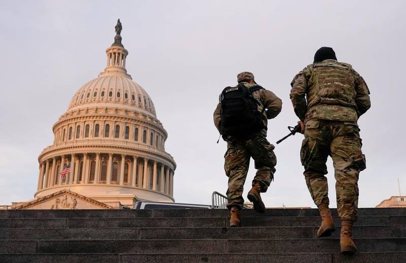 FILE PHOTO: National Guard members walk at the Capitol, in Washington, U.S., January 15, 2021. REUTERS/Joshua Roberts/File Photo
