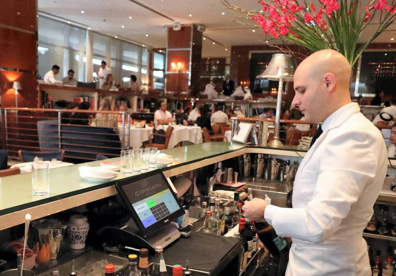 """A bar tendant serves customers at a restaurant in Dubai on August 30, 2018. - As temperature levels soar in Dubai, residents and tourists in the rich Emirate turn to a much favourite indoor outing during summer days: restaurants. From """"business lunches"""", to fresh decorations, Dubai's top restaurants compete to attract those costumers looking to beat the heat with a customised cool drink, or an award winning plate. (Photo by KARIM SAHIB / AFP)"""
