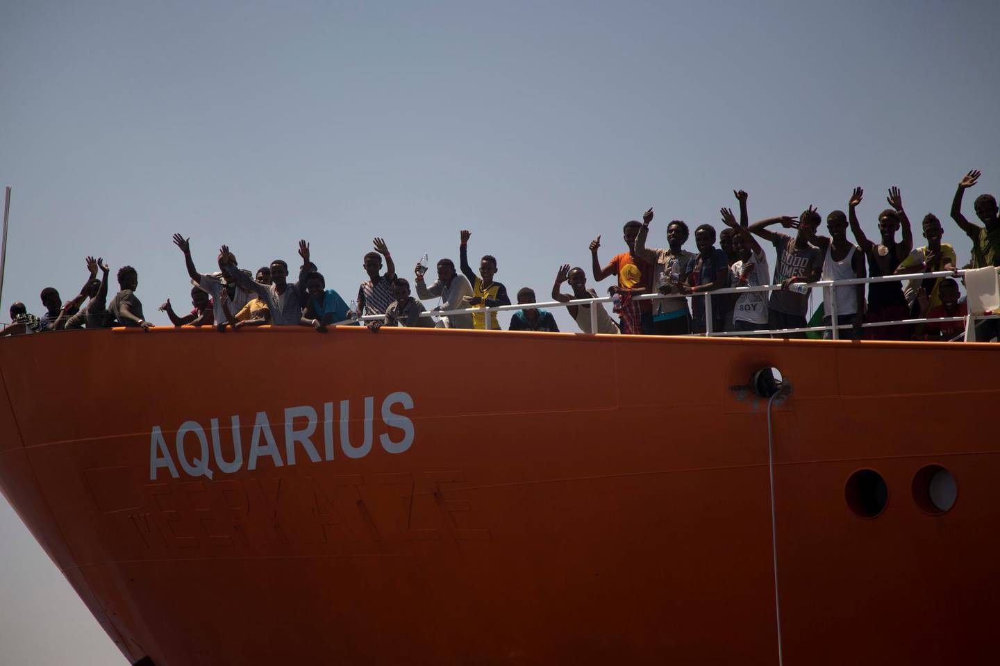 """In this photo taken on Sunday, Aug. 21, 2016, migrants wave from SOS Mediterranee Aquarius rescue ship, after being rescued by members of the Spanish NGO Proactiva Open Arms during an operation at the Mediterranean sea, about 12 miles north of Sabratha, Libya. Italy's new """"Italians first"""" government claimed victory Monday June 11, 2018, when the Spanish prime minister offered safe harbor to a private rescue ship after Italy and Malta refused to allow it permission to disembark its 629 migrant passengers in their ports. (AP Photo/Emilio Morenatti)"""