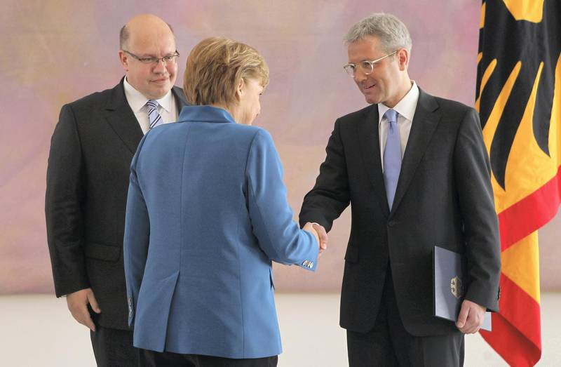 BERLIN, GERMANY - MAY 22:  German Chancellor Angela Merkel shakes hands with outgoing German Minister of the Environment Norbert Roettgen after he received his discharge papers from President Joachim Gauck (not pictured) as new Minister of the Environment Peter Altmaier (L) looks on during a ceremony at Schloss Bellevue palace on May 22, 2012 in Berlin, Germany. Merkel fired Roettgen following a disastrous election defeat for her party, the German Christian Democrats (CDU), in North Rhine-Westphalia, where Roettgen was the CDU lead candidate.  (Photo by Sean Gallup/Getty Images)