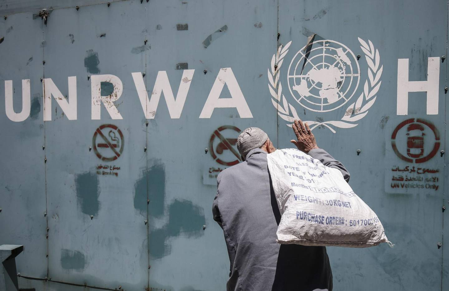 A Palestinian man stands in front of the emblem of the UN Relief and Works Agency for Palestine Refugees in the Near East (UNRWA) outside the agency's offices in Gaza City on July 31, 2018. / AFP PHOTO / SAID KHATIB
