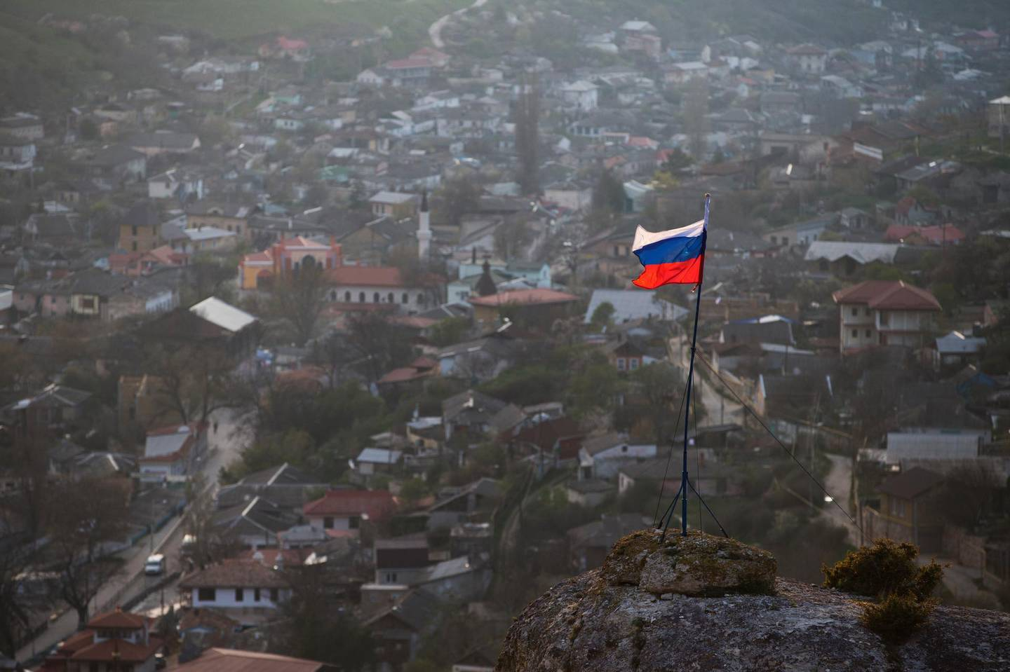 FILE - In this March 28, 2014 file photo, a Russian national flag flies on a hilltop near the city of Bakhchysarai, Crimea. The European Court of Human Rights decided Thursday Jan. 14, 2021, to start considering Ukraine's complaint against alleged human rights violations in the Russia-annexed Crimea. (AP Photo/Pavel Golovkin, File)