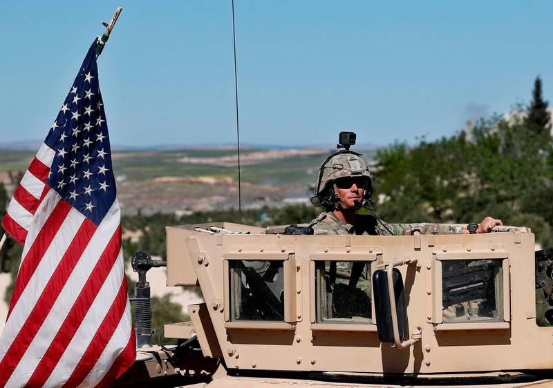"""FILE - In this Wednesday, April 4, 2018 file photo, a U.S. soldier sits on his armored vehicle on a road leading to the tense front line with Turkish-backed fighters, in Manbij, north Syria. Even as President Donald Trump mulls a U.S. pullout, insisting that the Islamic State is """"almost completely defeated,"""" the extremist group is showing signs of resurgence in Syria. Talk of a U.S. troop withdrawal has alarmed the Unites States' main ally in Syria, the Kurds, who fought alongside the Americans to roll back the Islamic State group. (AP Photo/Hussein Malla, File)"""