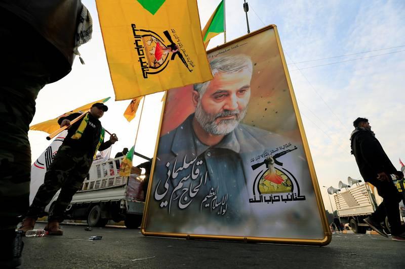 Kataib Hezbollah Iraqi militia hold the picture of the Iranian Major-General Qassem Soleimani, as they gather ahead of the funeral of the Iraqi militia commander Abu Mahdi al-Muhandis, who was killed in an air strike at Baghdad airport, in Baghdad, Iraq, January 4, 2020. REUTERS/Thaier al-Sudani