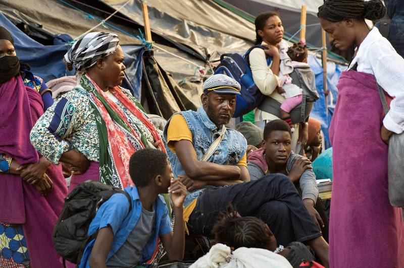 Hundreds of people from various African countries are gathered on the streets as they are evicted from the makeshift camp they are occupying around the Central Methodist Mission in Cape Town on March 1, 2020. - The refugees occupying the surroundings of a church in the city centre asked the UNHCR to intervene on their behalf after they said they felt no longer safe in South Africa due to high level of crime and xenophobia and are seeking help in being repatriated or deported to another country. (Photo by RODGER BOSCH / AFP)