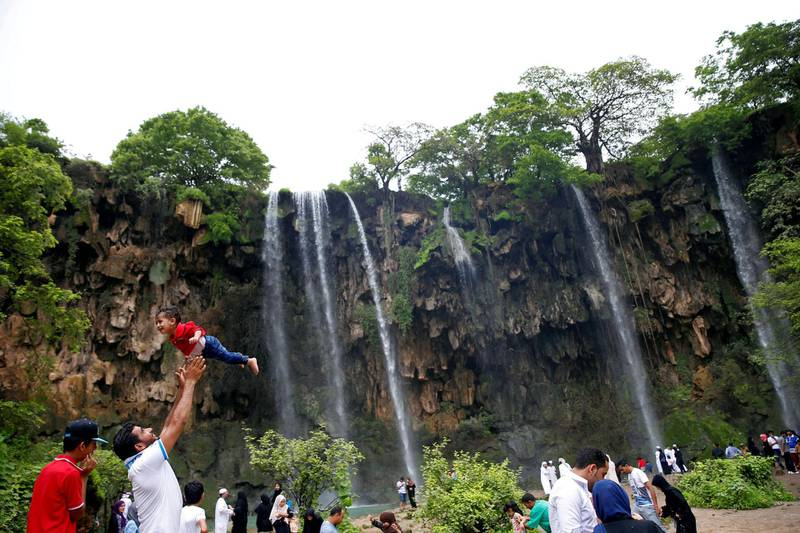 A tourist lifts up a boy as they visit waterfalls at Ayn Athum in Salalah, Dhofar province, Oman August 23, 2016. Picture taken August 23, 2016. REUTERS/Ahmed Jadallah