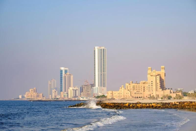 F4RGH6 View of skyline along corniche waterfront of  Ajman emirate in United Arab Emirates. Alamy
