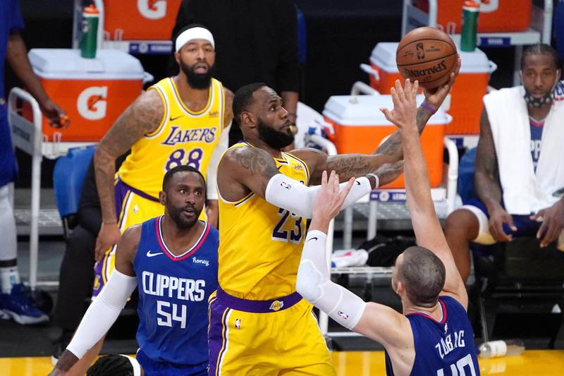 Dec 22, 2020; Los Angeles, California, USA;  Los Angeles Lakers forward LeBron James (23) shoots against LA Clippers forward Patrick Patterson (54) and center Ivica Zubac (40) in the fourth quarter at Staples Center. The Clippers defeated the Lakers. Mandatory Credit: Kirby Lee-USA TODAY Sports