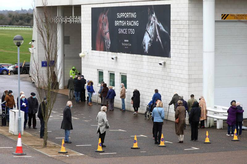 EPSOM, ENGLAND - JANUARY 11: Members of the public queue to receive the Oxford/AstraZeneca Covid-19 vaccine at the NHS vaccine centre that has been set up at Epsom Racecourse on January 11, 2021 in Epsom, England. The location is one of several mass vaccination centres in England to open to the public this week. The UK aims to vaccinate 15 million people by mid-February. (Photo by Dan Kitwood/Getty Images)