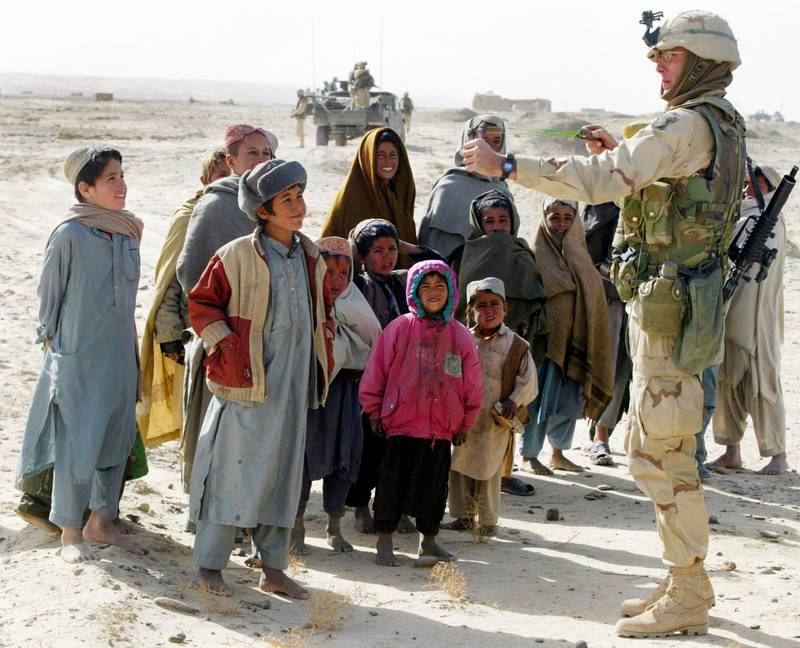 400626 06: 101st Airbornes 1st Sgt. Kerry Black from Westmoreland, Tennessee uses an Afghan childs sling shot February 6, 2002 as children crowd around him while he patrols on the outskirts of Kandahar, Afghanistan. The soldiers were on a reconnaissance and security patrol as well as looking for hidden ordinances. (Photo by Joe Raedle/Getty Images)