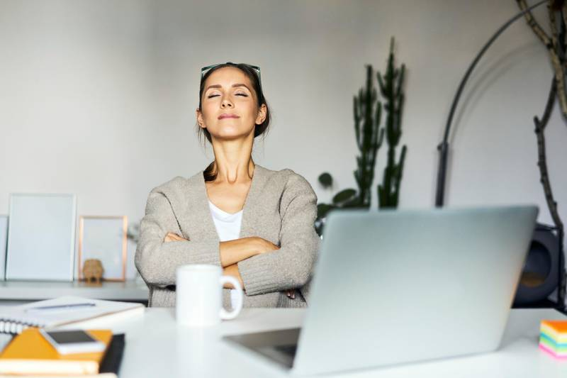 Young woman at home with laptop on desk having a break. Getty Images