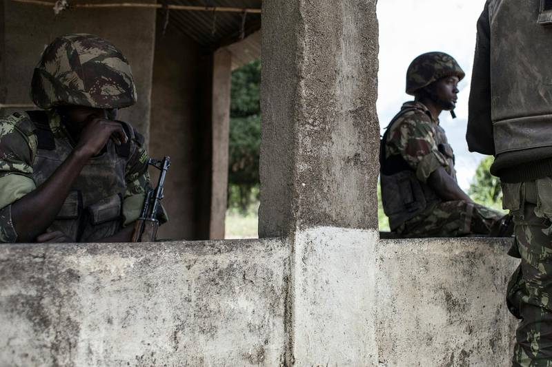 Mozambican Army soldiers stand at a checkpoint at the Vanduzi village on May 26, 2016 in the Gorongosa area, Mozambique. - Most of the population of Vanduzi have fled into the surrounding forests as the town has been the central point of ongoing sporadic violence between the Mozambican regular army and the main opposition party Mozambican National Resistance (RENAMO) militants. The Mozambican region of Gorongosa has been witnessing an increase in skermishes and sporadic clashes between the Mozambican regular army and the main opposition party Mozambican National Resistance (RENAMO) militants. (Photo by JOHN WESSELS / AFP)