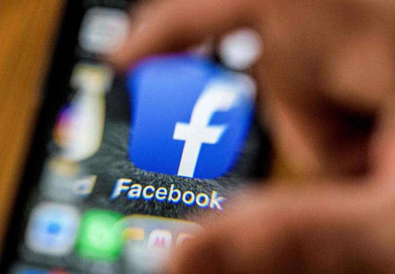"""An illustration picture taken through a magnifying glass on March 28, 2018 in Moscow shows the icon for the social networking app Facebook on a smart phone screen. Facebook said on March 28, 2018 it would overhaul its privacy settings tools to put users """"more in control"""" of their information on the social media website. The updates include improving ease of access to Facebook's user settings, a privacy shortcuts menu and tools to search for, download and delete personal data stored by Facebook. / AFP PHOTO / Mladen ANTONOV"""