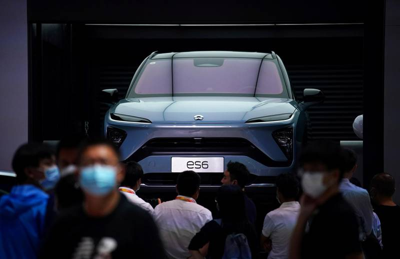 FILE PHOTO: People wearing face masks look at a Nio ES6 EV car at the Beijing International Automotive Exhibition, China, Sept. 27, 2020. REUTERS/Tingshu Wang/File Photo