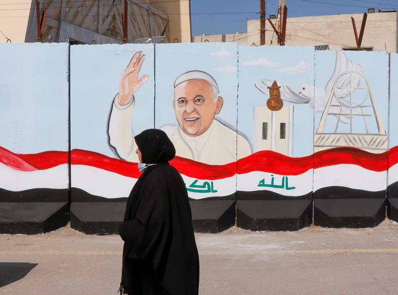 A woman walks near a mural of Pope Francis on the wall of a church upon his upcoming visit to Iraq, in Baghdad, Iraq February 22, 2021. REUTERS/Khalid al-Mousily     TPX IMAGES OF THE DAY