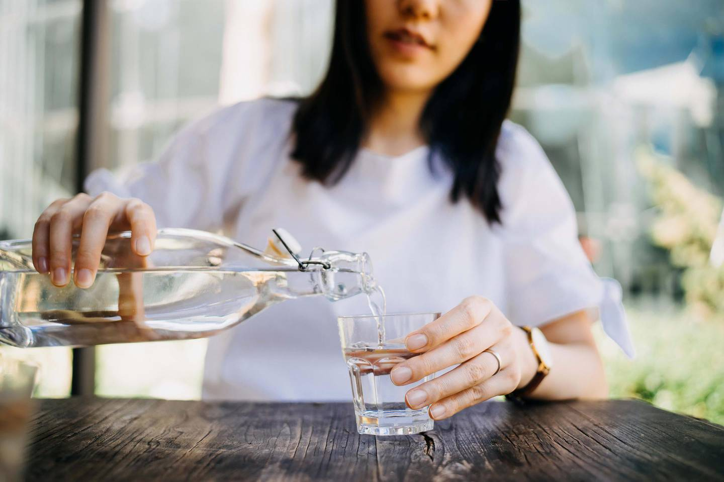 Woman pouring water from bottle into the glass at a outdoor cafe. Getty Images