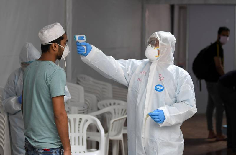 A foreign worker gets his body temperature tested for the novel coronavirus at a testing centre in the Naif area of the Gulf Emirate of Dubai, on April 15, 2020.  / AFP / KARIM SAHIB