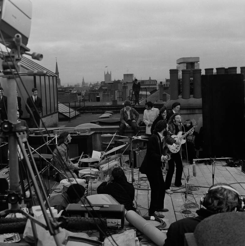 British rock group the Beatles performing their last live public concert on the rooftop of the Apple Organization building for director Michael Lindsey-Hogg's film documentary, 'Let It Be,' on Savile Row, London, UK, 30th January 1969; drummer Ringo Starr sits behind his kit, singer-songwriters Paul McCartney and John Lennon (1940 - 1980) perform at their microphones, and guitarist George Harrison (1943 - 2001) stands behind them. Lennon's wife Yoko Ono sits at right. (Photo by Evening Standard/Hulton Archive/Getty Images)