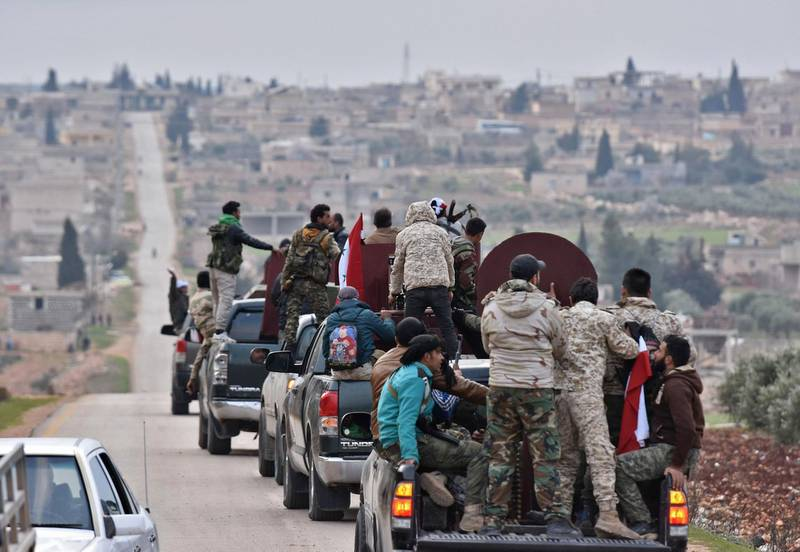 """TOPSHOT - A picture taken on February 20, 2018 shows a convoy of pro-Syrian government fighters arriving in Syria's northern region of Afrin. Kurdish forces said in a statement on February 20 that pro-regime fighters deployed to Syria's Afrin region will take up positions and """"participate in defending the territorial unity of Syria and its borders"""", countering Turkey's offensive on the area. / AFP PHOTO / George OURFALIAN"""
