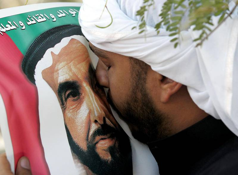 An Emirati man kisses the picture of Sheikh Zayed bin Sultan al-Nahayan during the Sheikh's funeral in Abu Dhabi 03 November 2004. Nahayan, the president and founding father of the United Arab Emirates, died 02 November 2004 after more than 30 years at the helm of his oil-rich country.      AFP PHOTO/RABIH MOGHRABI (Photo by RABIH MOGHRABI / AFP)