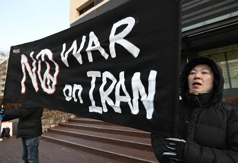 """South Korean activists hold a banner reading """"No war on Iran"""" during a rally denouncing the government's decision to send troops to the Strait of Hormuz, near the US embassy in Seoul on January 21, 2020. South Korea will send a naval destroyer and 300 troops to the Strait of Hormuz, its defence ministry said on January 21, after pressure from its ally the US in the face of tensions between Washington and Tehran. / AFP / Jung Yeon-je"""