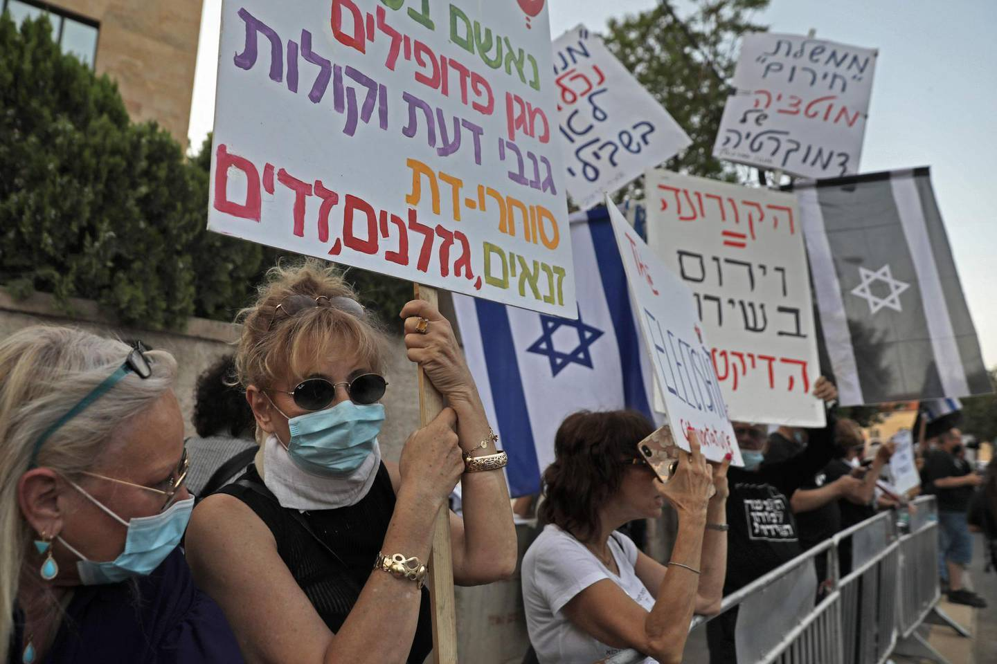 Israeli demonstrators, wearing protective masks amid the COVID-19 pandemic, carry placards during a demonstration against Prime Minister Benjamin Netanyahu in front of his residence in Jerusalem, on May 17 2020, as Israel's parliament swore in a new unity government. After more than 500 days without a stable government and three inconclusive elections, lawmakers in the 120-seat parliament approved a three-year coalition, with 73 voting for and 46 against. One member was absent. The new government was set to confront serious crises in its first weeks, including the economic devastation wrought by the coronavirus and a looming battle over Israel's possible annexation of large parts of the occupied West Bank. / AFP / MENAHEM KAHANA